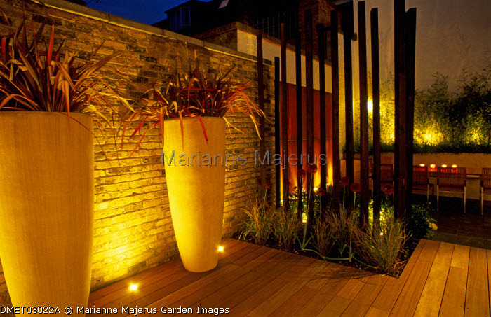Wooden posts, Phormium 'Rainbow Queen', large fibreglass containers