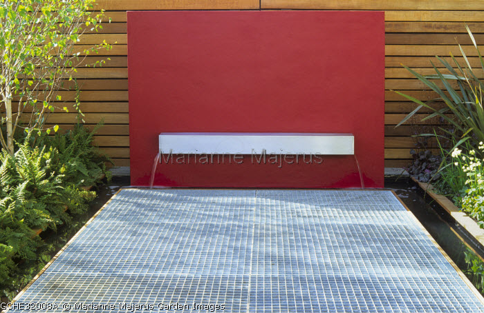 Fountain, metal grid, red painted wall