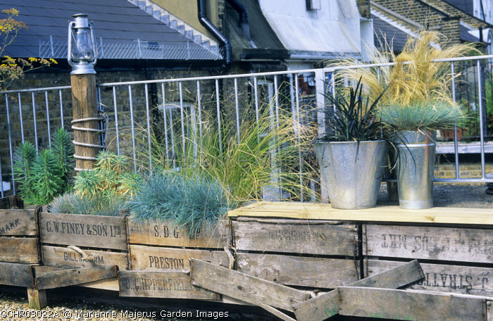 Seaside themed roof terrace, recycled wooden crates, Festuca glauca, Stipa tenuissima and Ophiopogon planiscapus 'Nigrescens' in metal containers, storm lantern on wooden post, metal railing