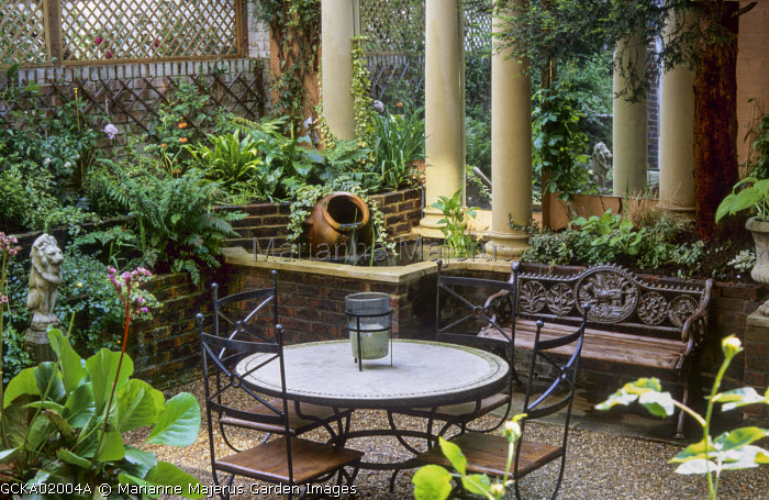 Table, chairs and bench on patio garden, stone columns