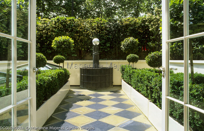 View from inside to courtyard garden outside, chequerboard paving, lead fountain, hedges of Buxus sempervirens and Prunus lusitanica