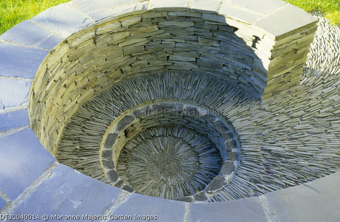 Coiled spiral dry-stone slate paddlestone wall, sunken seating
