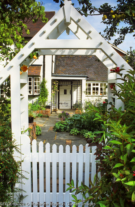 White Arch And Gate To Cottage Garden