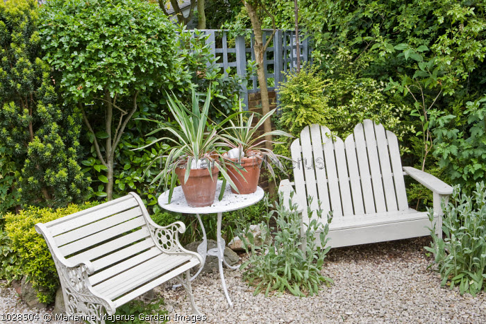 White painted bench, table & chair, phormiums in containers, seating area