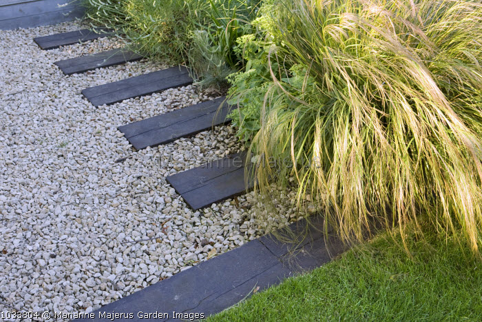 Timber stepping stone in gravel path, Stipa tenuissima, mowing strip