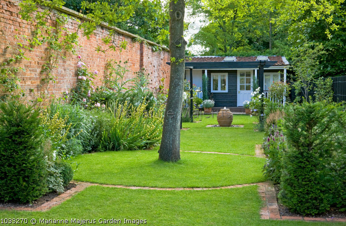 Oak tree, fountain in terracotta pot, view to summerhouse, lawn with brick edging