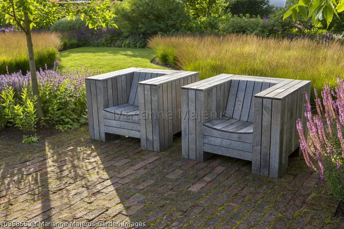 Wooden chairs by Piet Hein Eek on brick patio, drifts of Molinia caerulea