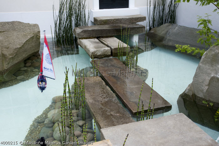 Front garden with moat planted with Equisetum and stepping stones giving access to the front door