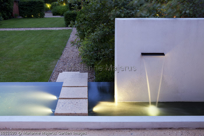 Stepping stones over pond, wall fountain