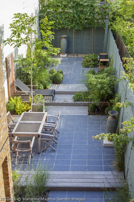 Overview of contemporary tiered town garden, table and chairs, steps, slate paving, garden 'rooms', Juglans regia