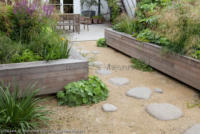 Stepping stones through grave to decked patio, raised timber beds with perennials, Deschampsia cespitosa 'Bronzeschleier', Alchemilla mollis, Lythrum salicaria