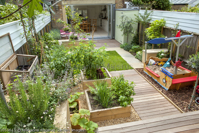 Overview Of Family Orientated Town Garden, Potager, Pirate Ship Sandpit,  Lawn, View