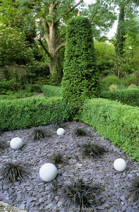 Clipped box and yew, slate chiiping mulch, stone balls, Ophiopogon planiscapus 'Nigrescens'