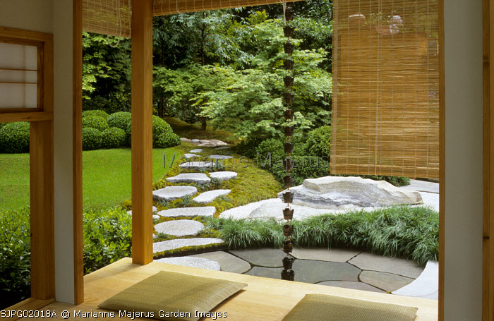 View through screens to Japanese garden, tea house, stepping stone path, acer