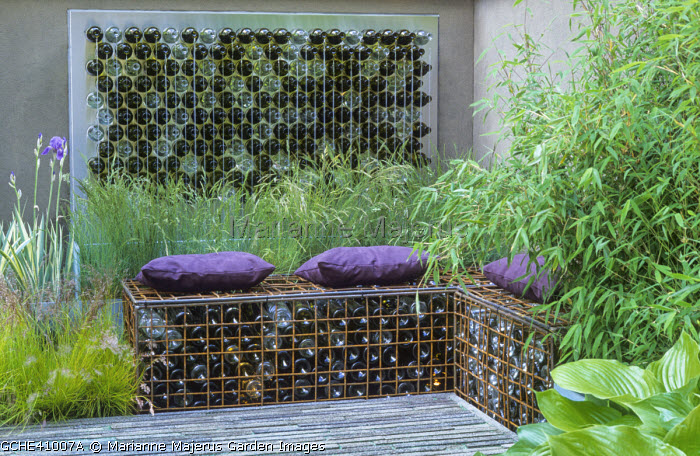 Gabions filled with bottles, recycled glass water feature, cushions, bamboo