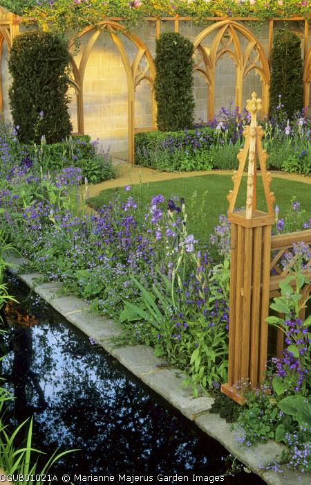Purple borders around lawn, Gothic 'cloister' pergola, irises