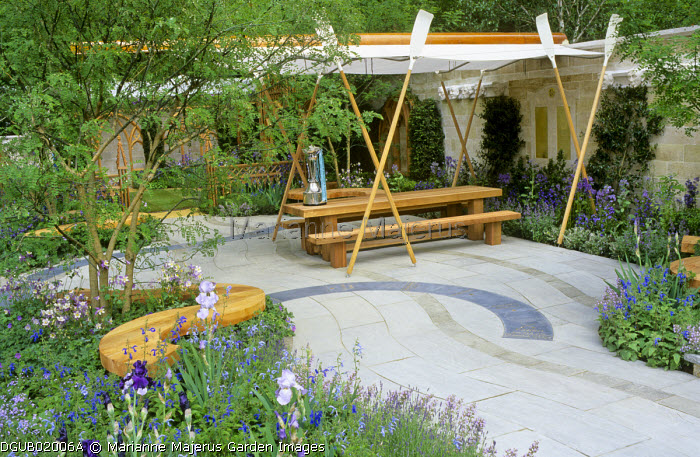 Wooden table and benches on Indian stone patio, fabric canopy supported by oars