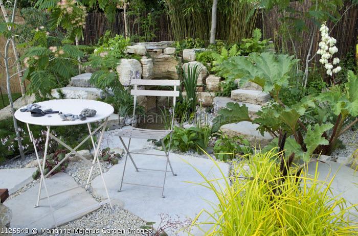 Rock garden with waterfall and pool, table and chair, Carex elata 'Aurea', Gunnera manicata, Albizia julibrissin, Purbeck capstone paving