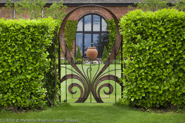 View through contemporary copper gate by Steve Myburgh in laurel hedge