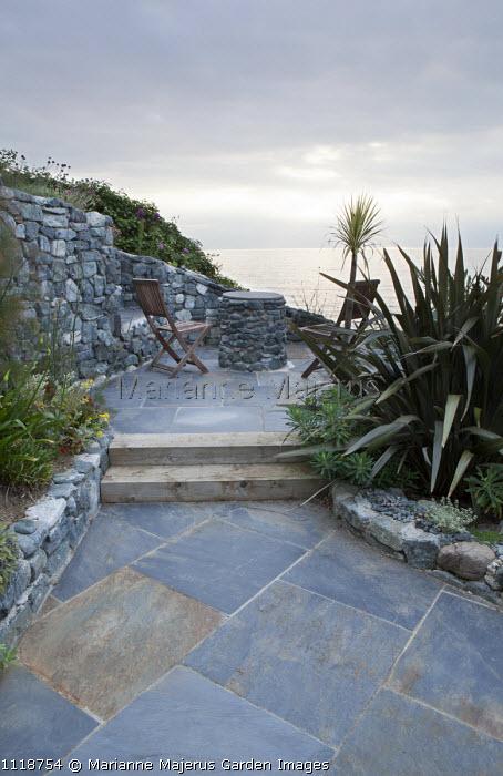 Chairs on patio overlooking sea, phormium, dry-stone walls