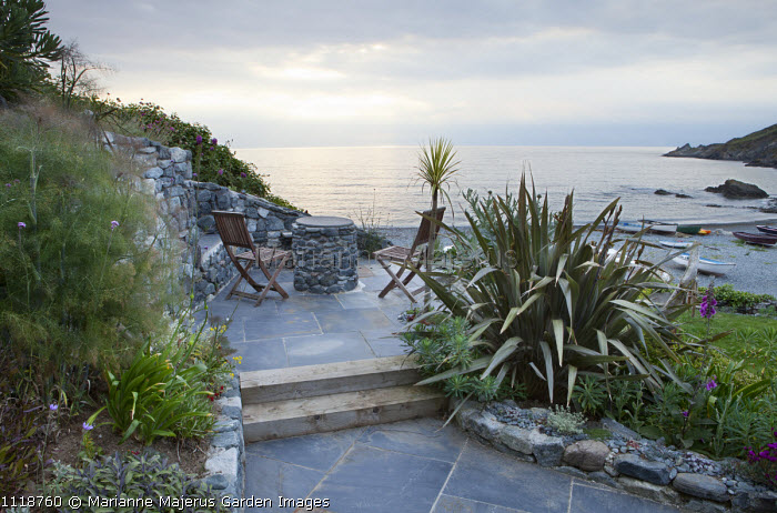 Chairs on patio overlooking Falmouth Bay and the sea, phormium, fennel, dry-stone walls