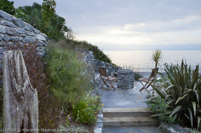 Chairs on patio overlooking sea, phormium, fennel, dry-stone walls