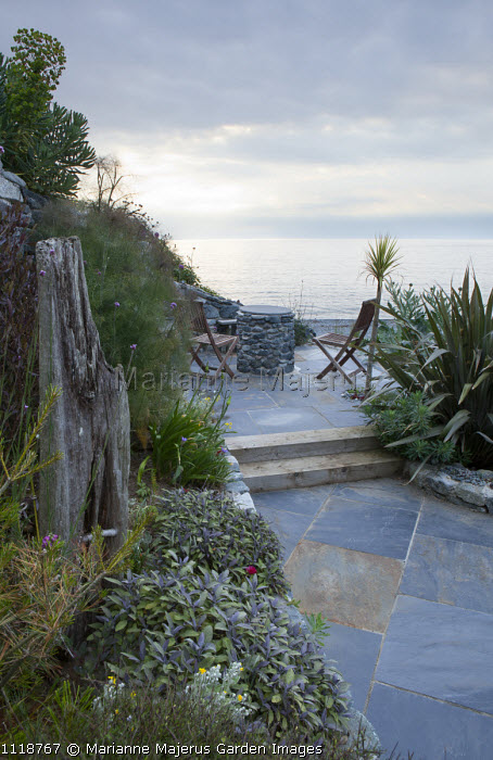 Chairs on patio overlooking sea, sage, fennel, phormium, driftwood