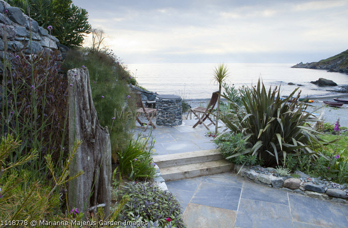 Chairs on patio overlooking Falmouth Bay and the sea, phormium, fennel, sage, Verbena bonariensis, driftwood
