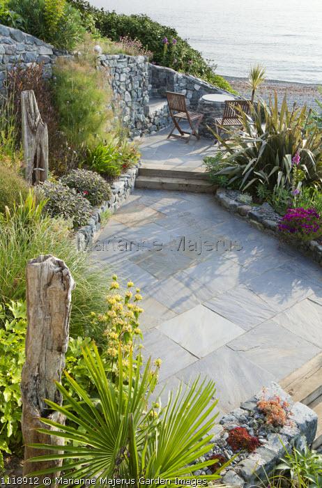 Slate terrace, table and chairs overlooking sea, stone edged patio, phormium, phlomis, driftwood