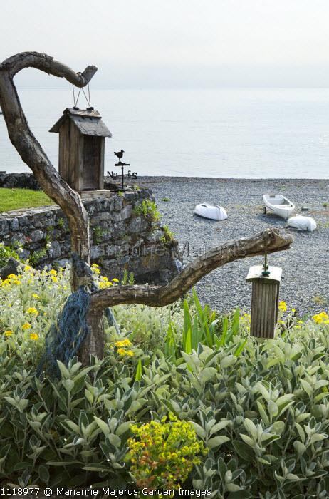 Porthallow Cove, shingle beach, boats, bird feeders on driftwood