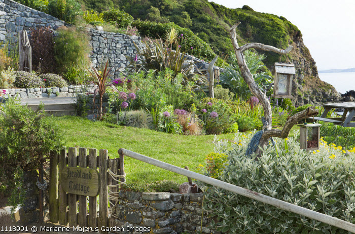 Seaside garden, gate with house name sign, bird feeders on driftwood