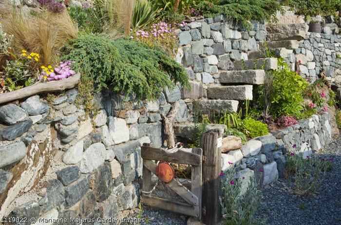 Stone steps along wall, driftwood gate