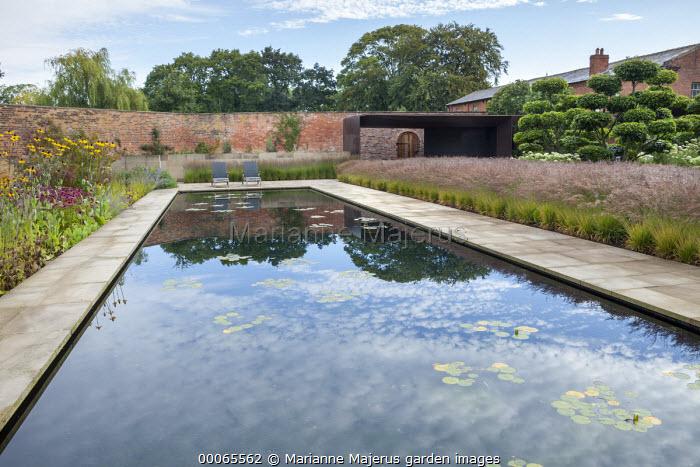 Reflection of blue sky in pond, Rudbeckia maxima, Echinacea purpurea, chairs, Molinia caerulea subsp. caerulea 'Poul Petersen', bronze pavilion