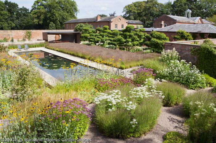 Overview of contemporary walled garden, formal pond, Molinia caerulea subsp. caerulea 'Poul Petersen', Echinacea purpurea, Rudbeckia maxima, cloud-pruned hornbeam trees, steel pavilion