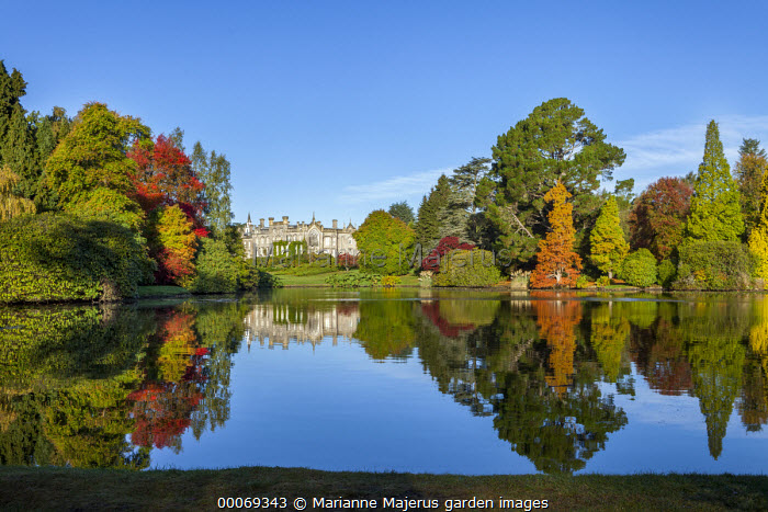View across lake to Neo-Gothic mansion, reflection of autumn trees in lake, Taxodium distichum