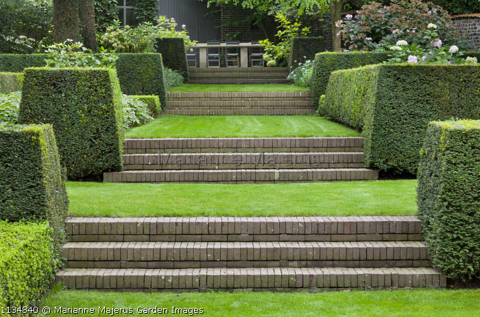 Formal sloping garden with tiered brick steps flanked by clipped yew hedges leading to table and chairs on upper terrace