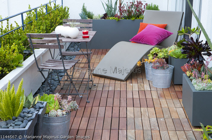 Contemporary recliner chair with cushions on decked balcony, wooden table and chairs, succulents in metal containers