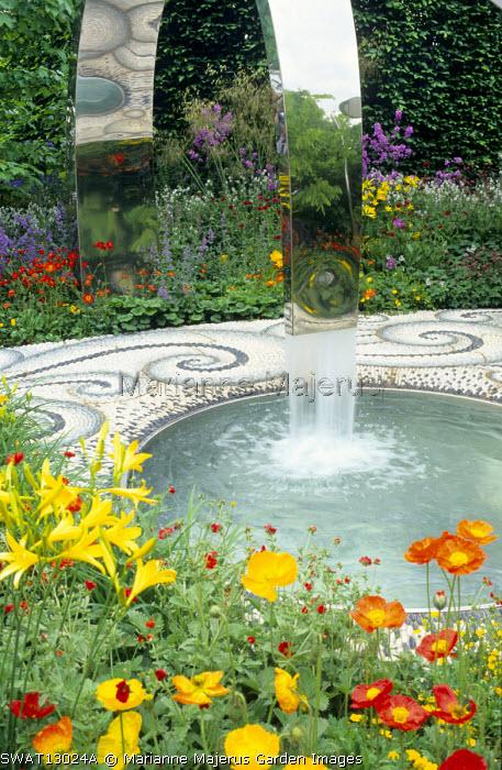 Stainless steel water feature, mosaic paving, hemerocallis, Papaver nudicaule