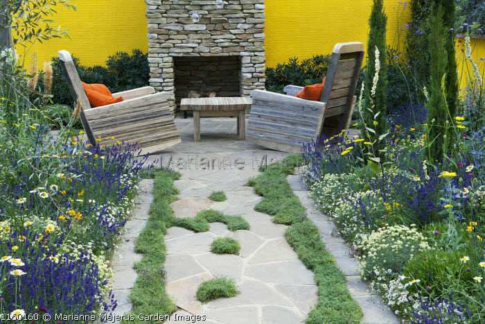 Mediterranean garden, thyme in paving cracks, wooden chairs made from recycled pallets in front of fireplace made from concrete 'stones', lavender