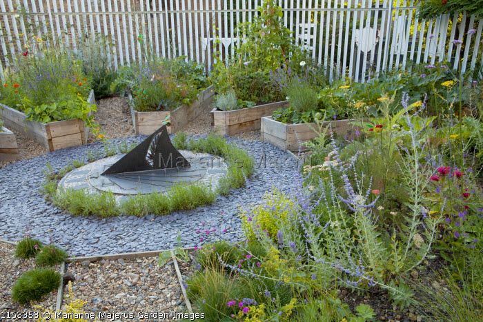 Circular potager garden, sundial, slate chippings, wooden raised beds, perovskia, chives, artichokes, lavender, fennel