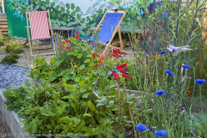 Deckchairs, nasturtiums in raised bed, Centaurea cyanus, fennel, feather bird ornaments, painted wall mural