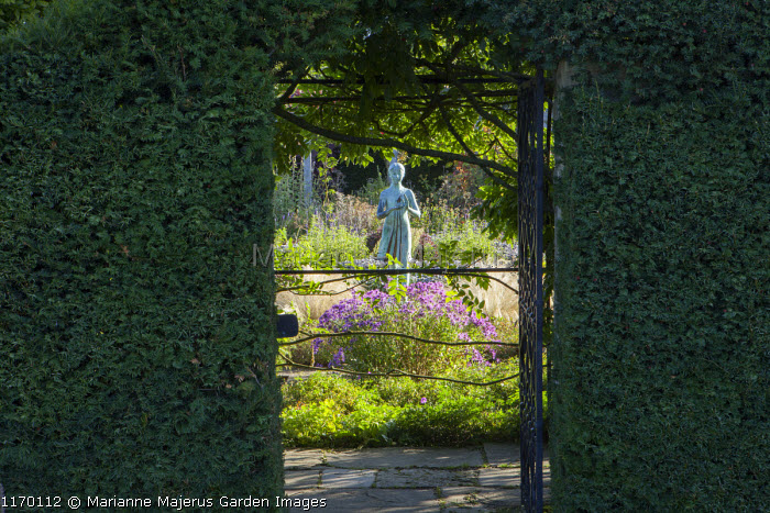 View though clipped yew hedge, gate, girl statue by Nathan David