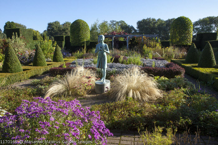 Statue of a girl in herb parterre garden surrounded by rows of box pyramid topiary in low clipped box hedge, aster, Stipa tenuissima