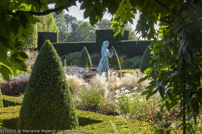 Formal garden, box pyramids, girl statue by Nathan David, Stipa tenuissima