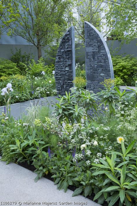 Stone sculpture by Tom Stogdon in sunken garden, Euphorbia x pasteurii, Anthriscus sylvestris, Salvia x sylvestris 'Mainacht', Mathiasella bupleuroides
