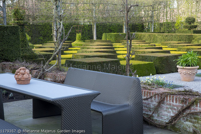 Contemporary furniture on patio, clipped yew and box topiary