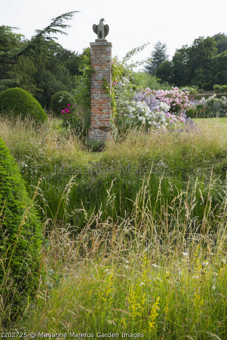 View across moat to walled garden with roses, yew topiary, long grass, stone eagle on brick wall