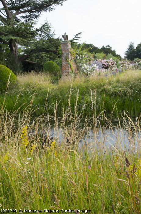 View across moat to walled garden with roses, long grass