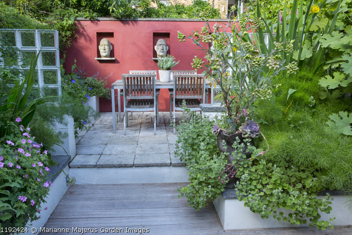 Sculpted heads from Stoned and Plastered in niches in red painted wall, table and chairs on patio, Ballota pseudodictamnus, Mathiasella bupleuroides, Iris pseudacorus, Ferula communis, Macleaya cordata, Echeveria agavoides 'Purple Pearl'