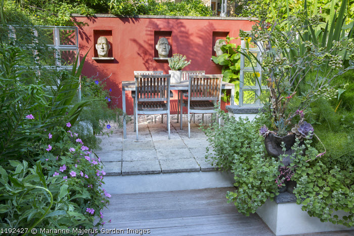 Sculpted heads from Stoned and Plastered in niches in red painted wall, table and chairs on patio, glass brick screen, Ballota pseudodictamnus, Mathiasella bupleuroides, Iris pseudacorus, Ferula communis, Echeveria agavoides 'Purple Pearl'